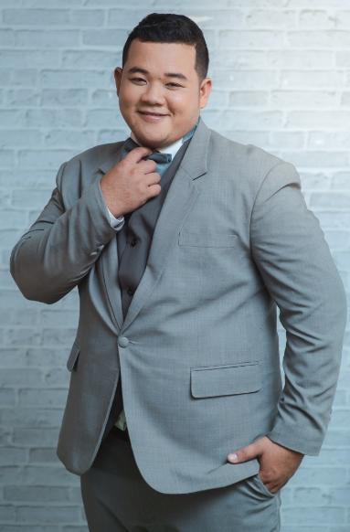 übergewichtiger Mann steht im Anzug vor einer Wand
