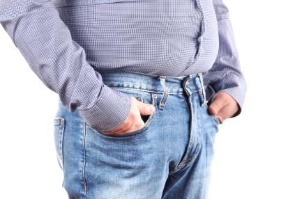 Übergewichtiger Mann trägt Jeans und ein enges Hemd