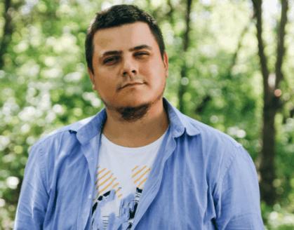 Mann mit blauem Hemd in Übergröße steht vor einem Wald