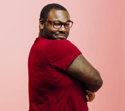 dunkelhäutiger Mann mit Brille trägt rotes T-Shirt in Übergröße